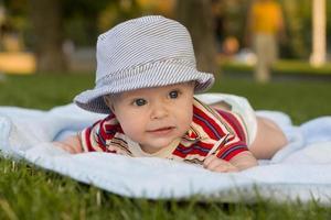 bebê deitado de bruços em um cobertor no parque
