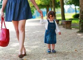 mãe jovem feliz e garota adorável criança andando através da soma