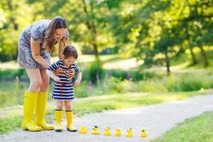 mãe e filha adorável em botas de borracha amarelas foto