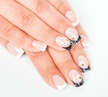 mãos bonitas com manicure em uma luz de fundo foto