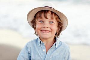 garoto positivo na praia foto