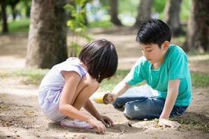 pequena criança asiática jogando areia no parque foto