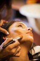 esteticista de salão aplica maquiagem a um cliente foto