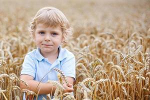menino feliz se divertindo no campo de trigo no verão foto