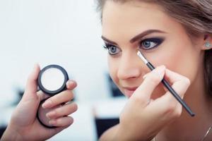 um maquiador colocando sombra sobre uma mulher foto