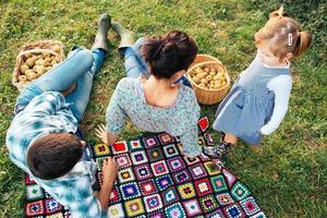 família feliz de três deitado na grama no outono foto