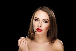 jovem morena linda com lábios vermelhos e maquiagem foto