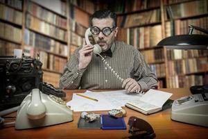 empregado com óculos falando ao telefone no escritório foto