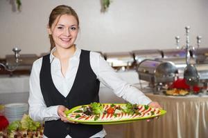 empregado de serviço de catering posando com bandeja para buffett foto