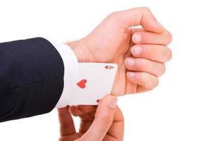empresário com cartão ás escondido debaixo da manga. foto