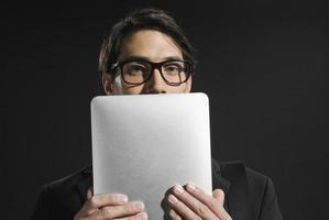 jovem empresário segurando o rosto do tablet parcialmente obscurecido foto