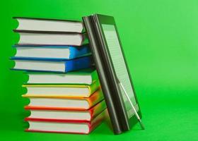 leitor de livros eletrônicos com pilha de livros impressos foto