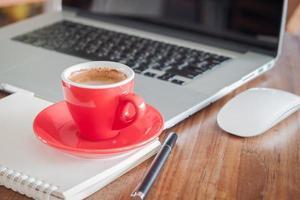 xícara de café vermelho com o bloco de notas e laptop foto
