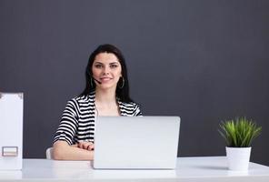 mulher de negócios bonita trabalhando na mesa com fone de ouvido e foto