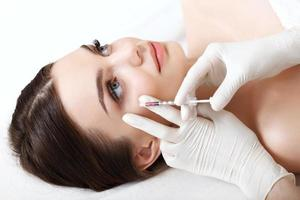mulher bonita recebe injeções. cosmetologia. rosto bonito foto