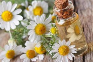 óleo perfumado de camomila em macro de garrafa de vidro horizontal foto
