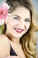 menina com um sorriso lindo fermento flor nas mãos foto