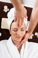jovem mulher recebendo massagem na cabeça no spa foto