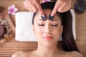 mulher bonita, tendo uma massagem na cabeça bem-estar com pedras foto