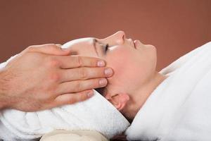 mulher relaxada, recebendo massagem na cabeça no spa foto