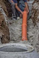 trabalhadores, colocando tubos de pvc no fundo da vala 2