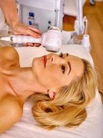 jovem mulher recebendo massagem facial elétrica foto