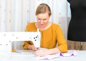 mulher que trabalha na máquina de costura na fábrica.