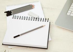 dois blocos de desenho, lápis e borracha na mesa de madeira branca foto