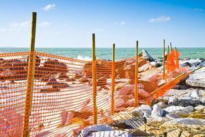 canteiro de obras com grade de segurança laranja à beira-mar foto