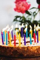 bolo de aniversário com muitas velas acesas