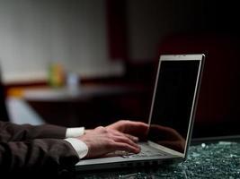 mãos e laptop do homem foto