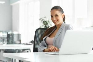 bela empresária em seu escritório, trabalhando no computador portátil foto
