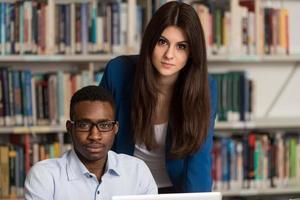 casal de estudantes com laptop na biblioteca foto