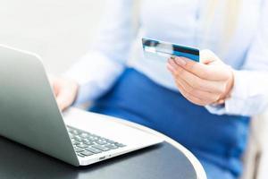 mulher com laptop e cartão de crédito foto