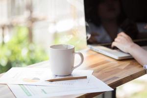 xícara de café e empresária trabalhando com documentos e laptop