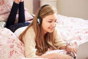 adolescente deitado na cama usando laptop usando fones de ouvido foto