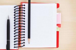 mesa de escritório com o bloco de notas em branco, caneta e lápis foto