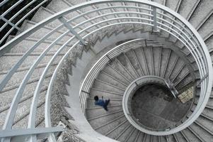 homem de camisa azul, descendo uma escada em espiral