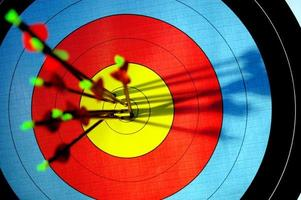 flechas no olho de touros do alvo de tiro com arco foto