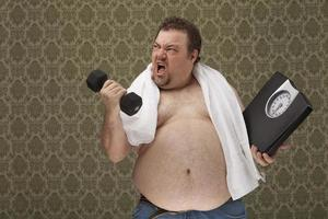 excesso de peso masculino segurando escalas trabalhando duro para perder peso foto