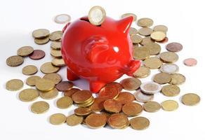 cofrinho vermelho cercado por moedas foto