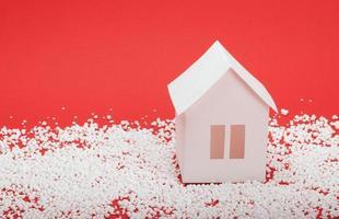 casa de papel na neve em fundo vermelho foto