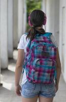 menina adolescente da escola com uma mochila e fones de ouvido