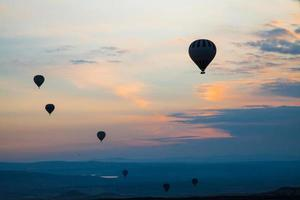 balões de ar quente no nascer do sol silhueta ao fundo foto