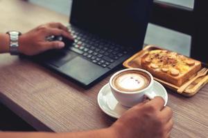 empresário está trabalhando com o laptop, segurando um telefone móvel foto