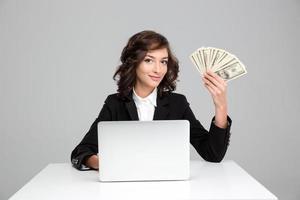 bela jovem usando laptop e mostrando dinheiro foto