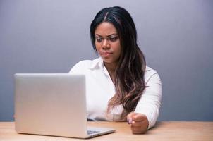 empresária africana com raiva usando laptop