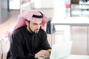 retrato de um homem de negócios árabe inteligente usando laptop foto