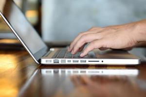 Feche as mãos do homem usando o laptop. foto