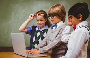 crianças da escola usando o laptop na sala de aula foto